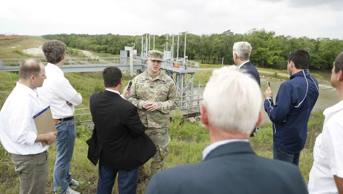 Captain Charles Ciliske with the US Army Corps of Engineers is audio recorded by court reporter David Lee as U.S. Judge Charles Lettow, foreground, listens to his testimony on the top of Barker Reservoir, as the homeowners suing after Harvey went out to view homes in the Addicks and Barker Dam areas, in Houston, Wednesday, May 8, 2019.