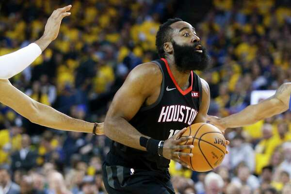 Houston Rockets guard James Harden (13) works the ball toward the basket against the Golden State Warriors center Kevon Looney (5) defending during the first half of Game 5 of the NBA Western Conference semifinals at Oracle Arena on Wednesday, May 8, 2019, in Oakland.