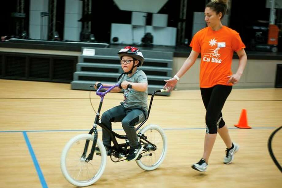 Jayson Brooks of Coleman, 10, mimics the sound of an engine while riding a bicycle for the first time after participating in the iCan Bike Camp, hosted by The Arc of Midland, on Wednesday afternoon at Midland Evangelical Free Church. For more photos go to www.ourmidland.com. (Katy Kildee/kkildee@mdn.net)