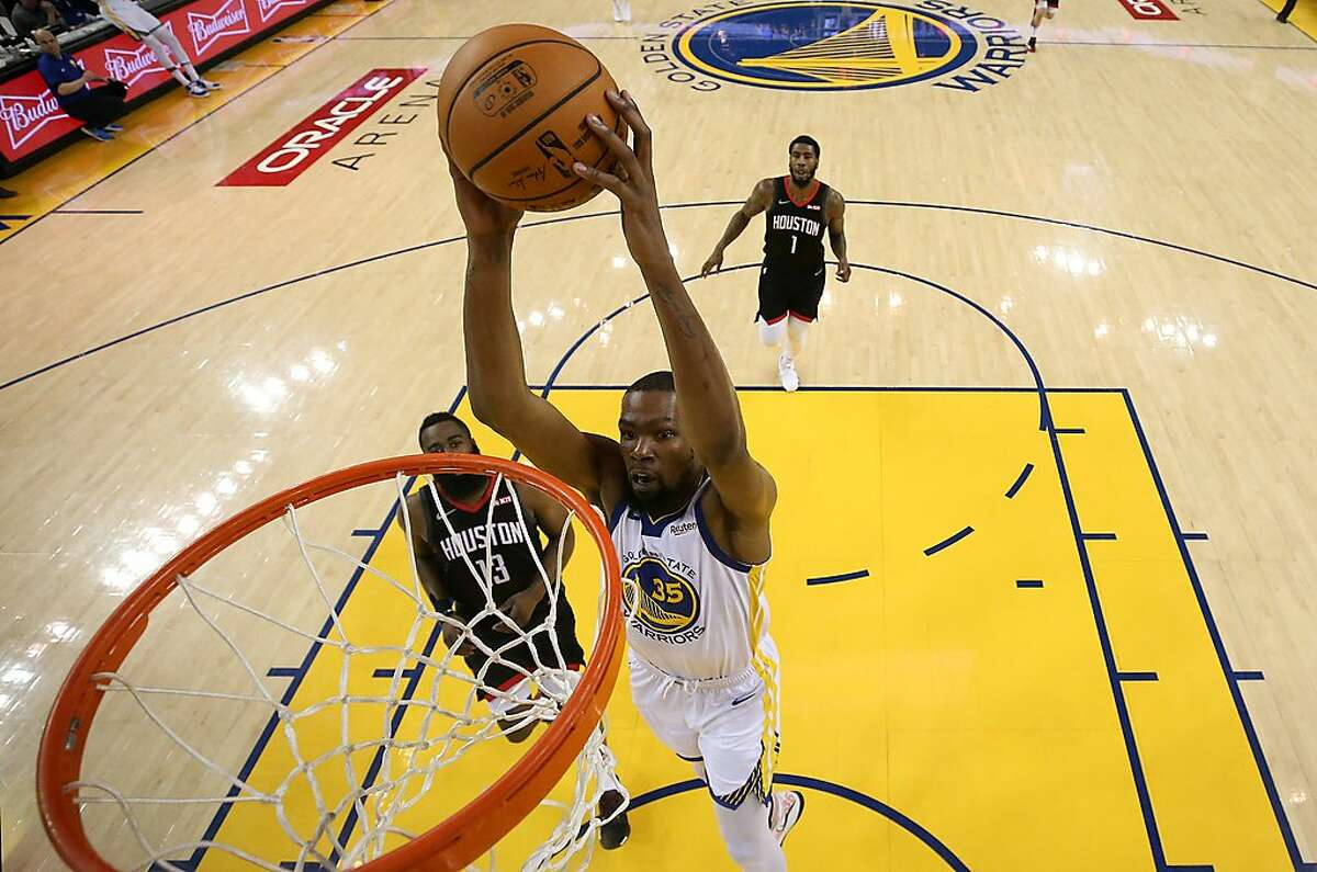OAKLAND, CALIFORNIA - MAY 08: Kevin Durant #35 of the Golden State Warriors dunks the ball on James Harden #13 of the Houston Rockets during Game Five of the Western Conference Semifinals of the 2019 NBA Playoffs at ORACLE Arena on May 08, 2019 in Oakland, California. NOTE TO USER: User expressly acknowledges and agrees that, by downloading and or using this photograph, User is consenting to the terms and conditions of the Getty Images License Agreement. (Photo by Ezra Shaw/Getty Images)