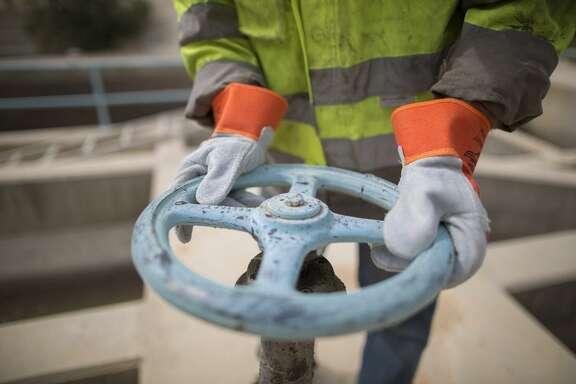 An employee of a sewage treatment plant uses a handwheel.