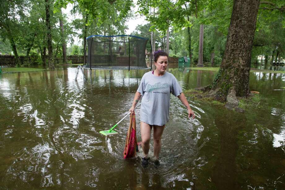 Jennifer Wilson walks in her flooded yard to retrieve floated items on Wednesday, May 8, 2019, in Porter. The Wilson family received about a foot of flood water in the house from the Tuesday rain. Wilson and his wife, Jennifer, has experienced three hurricane floods, including Harvey, in the past but none of them had more water in the house than Tuesday's rain. The family lived four months without carpet after Harvey flood and they finally started to feel stable about nine months ago. Photo: Yi-Chin Lee, Staff Photographer / © 2019 Houston Chronicle