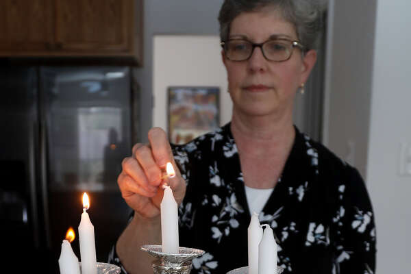 Lisa Klein lights the candles as she prepared for Shabbat, before her weekly celebration commenced, Friday, Feb. 22, 2019, in Houston.