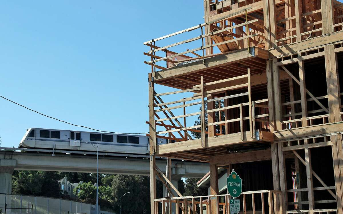 A BART train moves by new, luxury condo construction on Trinity Avenue in Walnut Creek, Calif., on Sunday, May 5, 2019. State Sen. Scott Wiener's SB50, besides allowing denser housing near transit, would wipe out single-family zoning in many suburban cities and allow apartment construction in such areas.