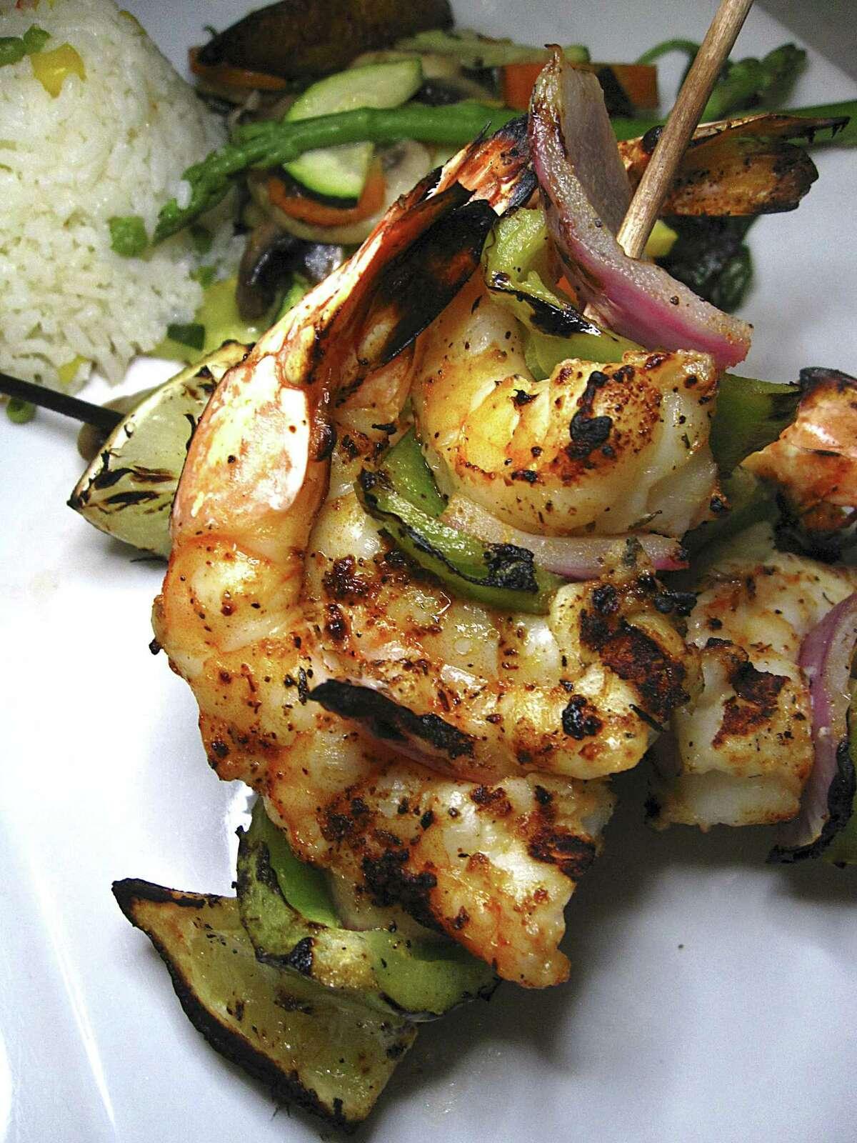 Grilled shrimp are served on skewers with vegetables for camarones a la parrilla at SoLuna.
