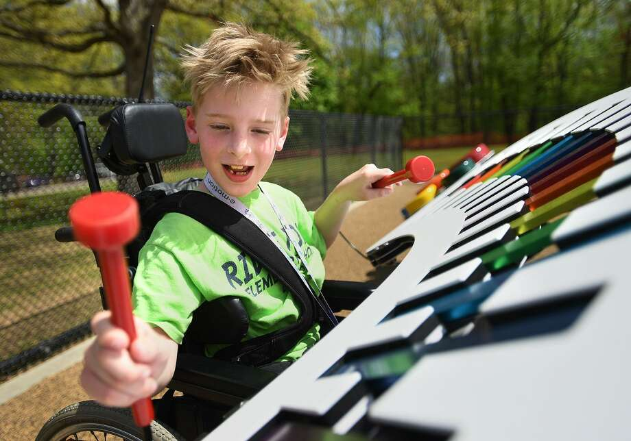 Second-grader Isaiah Lamb, 7, tries out the xylophone following the ribbon-cutting for a on the new handicapped-accessible playground at Ridge Road Elementary School in North Haven  Wednesday, May 8, 2019. Isaiah's mother, Erin, is a member of the school's PTA that planned the project. Photo: Brian A. Pounds / Hearst Connecticut Media / Connecticut Post