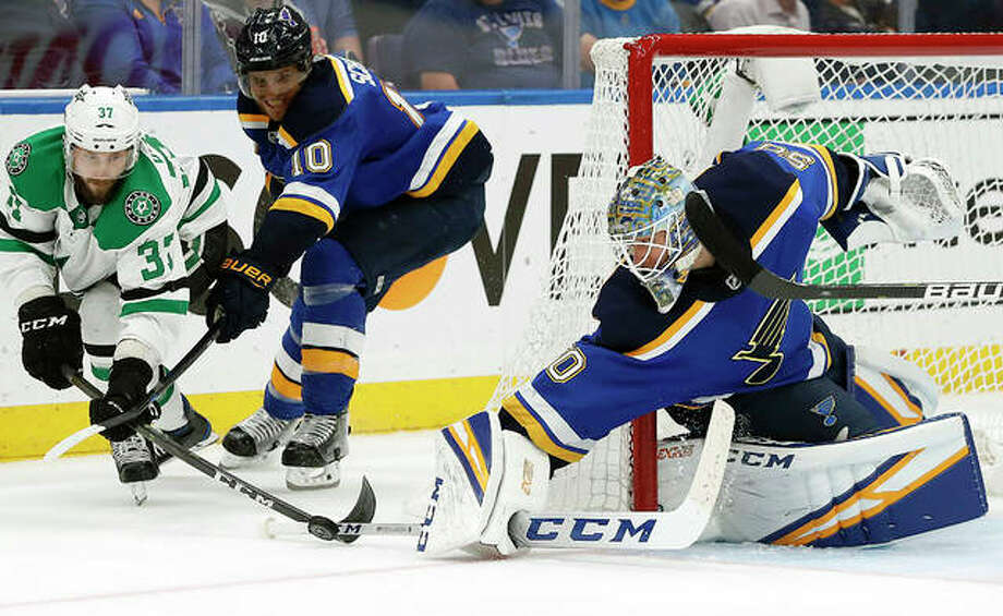 Blues goalie Jordan Binnnington slaps the puck away from the Stars' Justin Dowling (37) as Blues defender Brayden Schenn watches in Game 7 of their Western Conference semifinal series Tuesday in St. Louis. Photo: Jeff Roberson | AP Photo