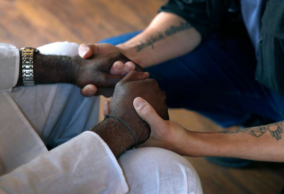 "Tambu Kisoki (left) welcomes a participant to a ""ritual for healthy masculinity"" workshop on sexual consent by the Urban Healers all-men's group, in Oakland, Calif. on Saturday, April 27, 2019. Photo: Paul Chinn / The Chronicle"