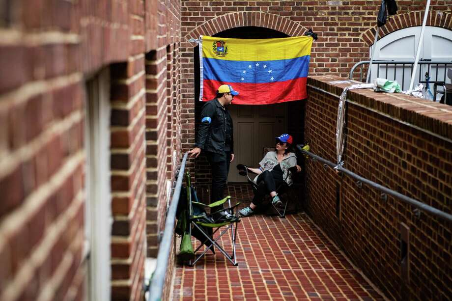 Supporters of opposition leader Juan Guaidó sit at the back of the Venezuelan embassy in Washington to block members of Code Pink and other activists who support President Nicolás Maduro from entering on May 4, 2019. Photo: Washington Post Photo By Salwan Georges / The Washington Post