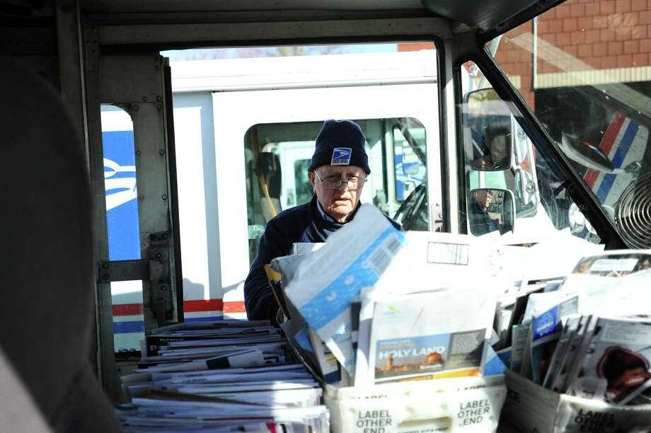 Tony Spadaccini, 81, puts the last bin of mail into his truck outside the Stamford Post Office on Camp Ave. on Tuesday, April 24, 2018. On Saturday, May 11, U.S. Postal Service letter carriers will conduct the largest one-day food drive in the nation. To participate, place a box or can of non-perishable food next to your mailbox before your letter carrier delivers mail. The donations are sorted and delivered to a food bank. Photo: Michael Cummo / Hearst Connecticut Media / Stamford Advocate