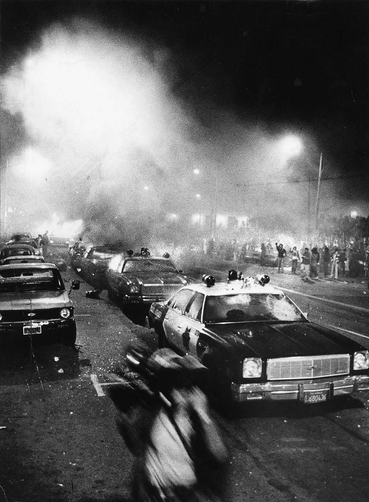 WHITE NIGHT/22MAY79/MN/STOREY - OVERALL OF THE POLICE CARS ON FIRE AT CIVIC CENTER. THE PERSON IN THE FOREGROUND WAS A NEWS CAMERAPERSON RUNNING. THE RIOT STARTED AFTER THE VERDICT FOR DAN WHITE CAME DOWN FROM THE COURT. RIOTS STARTED UP OUTSIDE CIVIC CENTER, NEAR CITY HALL. Dan White, George Moscone, Harvey Milk. PHOTO BY JOHN STOREY WHITE NIGHT RIOTS jonestown40