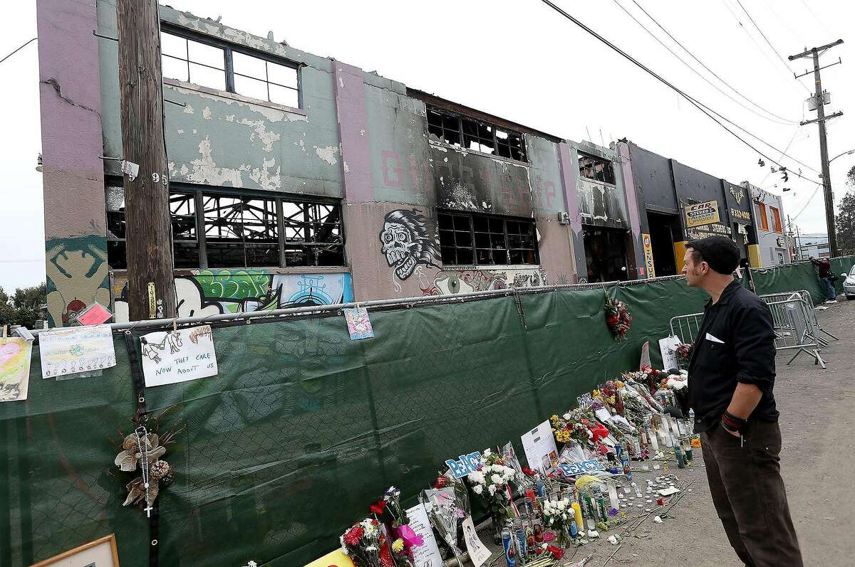 A mourner pays his respects as Investigators carry on their work at the Ghost Ship warehouse in Oakland, Calif., on December 13, 2016. Thirty-six people died in the December 2, 2017, fire. (Jane Tyska/Bay Area News Group/TNS)