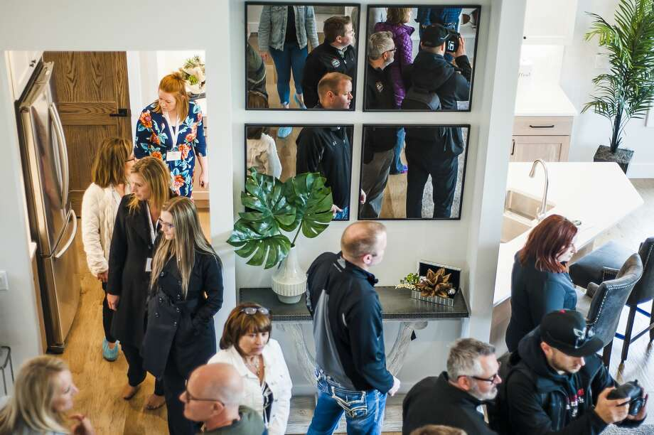 Guests tour a custom built home by Greystone Homes, the proceeds of which will benefit Midland's Open Door programs assist homeless mothers, during a ribbon cutting ceremony to commemorate its completed construction on Wednesday, May 8, 2019 at 3060 Alderberry Court in Midland. (Katy Kildee/kkildee@mdn.net) Photo: (Katy Kildee/kkildee@mdn.net)