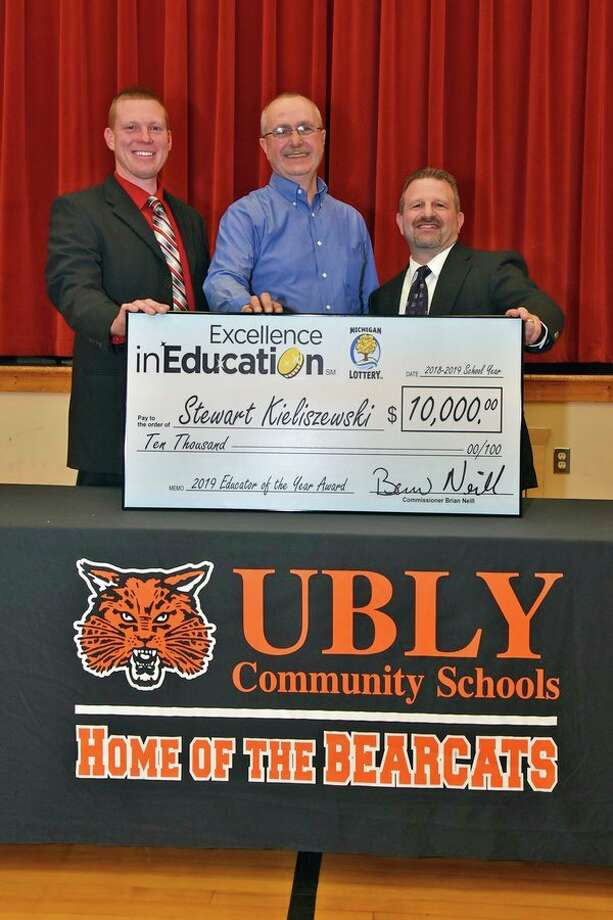 Michigan Lottery Educator of the Year Stewart Kieliszewski (second from left), poses for a photo with, from left, Ubly Principal Jeremy Warner, Michigan Lottery Commissioner Brian O. Neill, and Ubly Superintendent Joe Candela (Courtesy Photo) / @2017