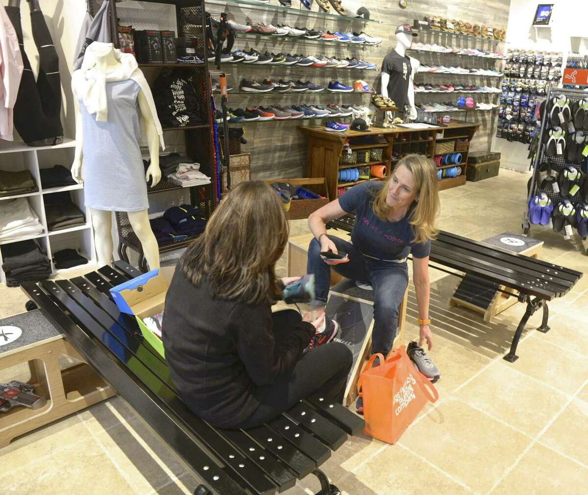 Megan Searfoss, owner of the Ridgefield Running Co., right, works with Jodi Costenbader, of Redding, who was shopping for athletic shoes. Searfoss started the Run Like A Mother 5K in 2008. Thursday, May 9, 2019, in Ridgefield, Conn.
