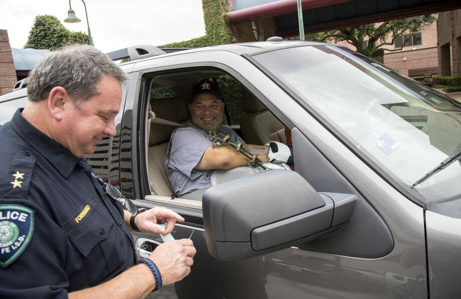 John Barnes, right, the Santa Fe ISD police officer who was shot during the mass shooting at Santa Fe High School, smiles after Gary Forward, assistant police chief of Santa Fe ISD, cut the hospital ID band off Barnes' wrist after he was discharged from TIRR on Wednesday, June 20, 2018, in Houston. Barnes credits Forward with saving his life, because he put a tourniquet on him after he was shot in the arm with a shotgun. Photo: Jon Shapley/Staff Photographer
