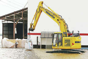 """A worker prepares to guide a large sandbag into place late Wednesday at the site of a flood related foundation collapse described by sources as """"a hole"""" in the southwest corner of the Ardent Mills complex. The wooden box-type structure was erected earlier in the week around the """"hole"""" to prevent waves and water from making it worse. A large trackhoe was brought in Wednesday evening to help workers in waders reinforce and block the water from the damaged area. Workers were still finishing up as the sun rose Thursday. The area of the damage is not far from the giant American flag painted on the white silos and is known to employees as the break area at the mill."""