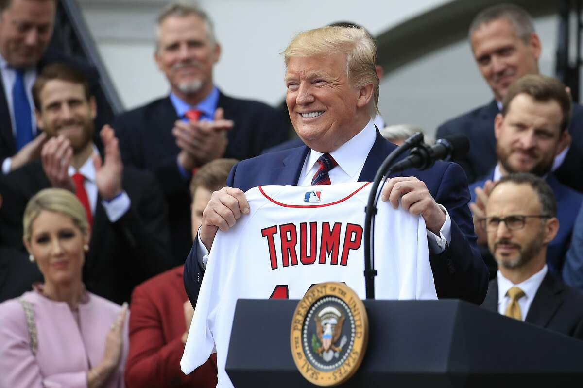 President Donald Trump shows off a Red Sox jersey presented to him during a ceremony welcoming the Boston Red Sox the 2018 World Series baseball champions to the White House, Thursday, May 9, 2019, in Washington. (AP Photo/Manuel Balce Ceneta)