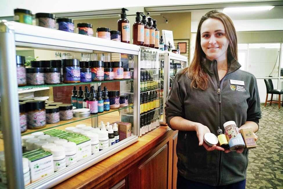 Erika Fallon, supervising pharmacist at Fallon Wellness Pharmacy, holds items that contain CBD at Fallon Wellness Pharmacy on Thursday, May 9, 2019, in Latham, N.Y. From left to right in Fallon's hand are a CBD salve, a CBD oil, CBD Gummy Bears, and CBD hemp soft gels. (Paul Buckowski/Times Union)