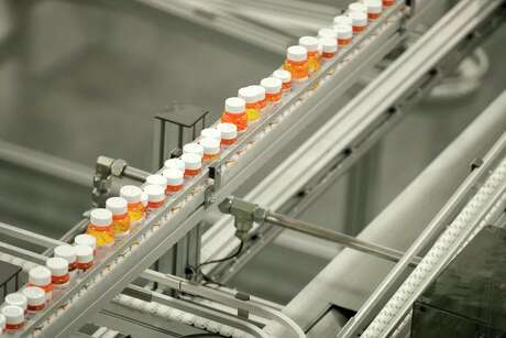 Bottles of medicine ride on a belt at the Express Scripts mail-in pharmacy warehouse in Florence, N.J.