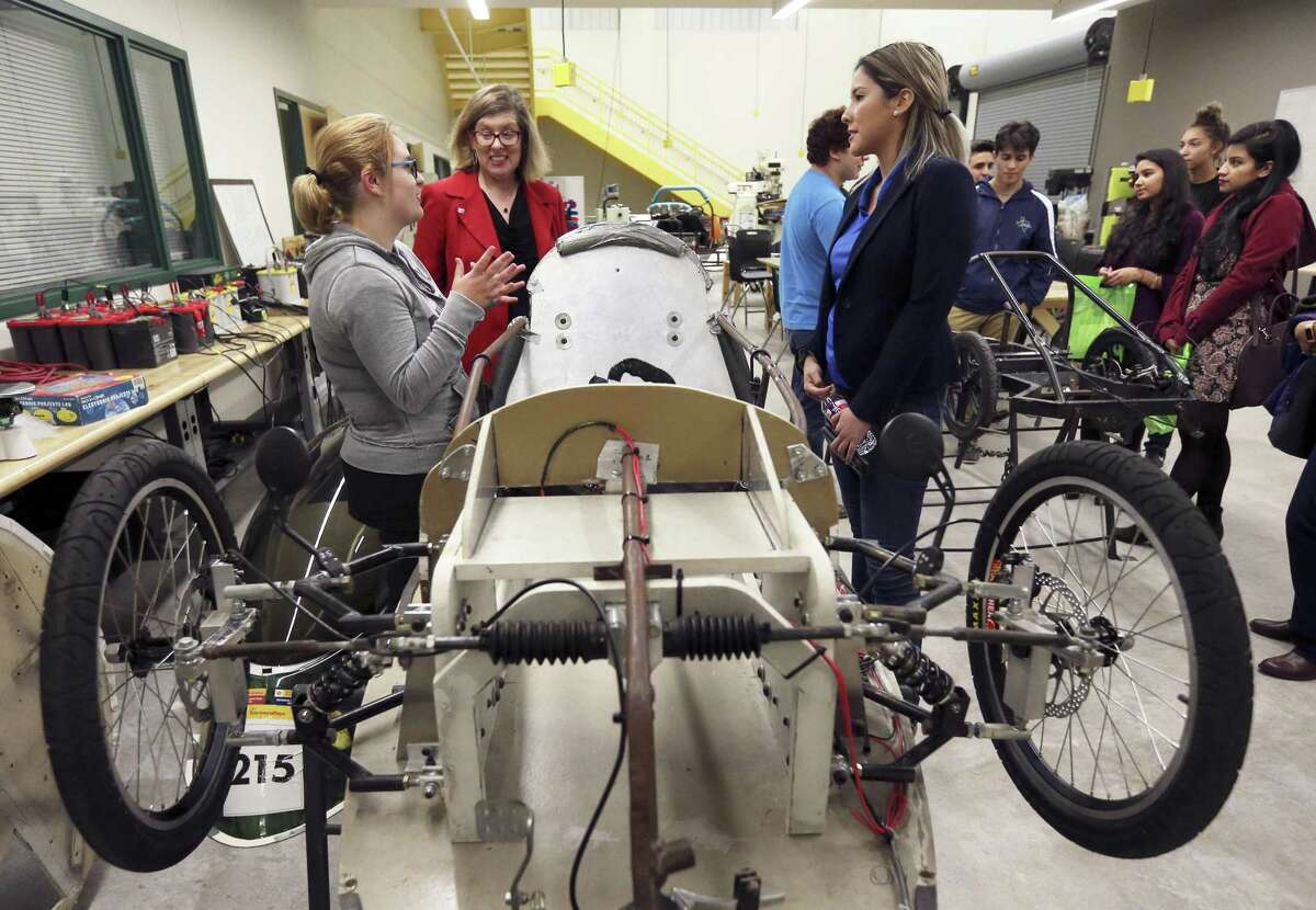 Southwest High School senior Ellora Wilson (left) talks to guests such as Girls Inc. of San Antonio president and CEO Lea Rosenauer (center) about her work on a hydrogen fuel cell car project at CAST STEM during an event in 2017. A $2 million gift announced Thursday will help the career-themed high school move to its own building. (Kin Man Hui/San Antonio Express-News)