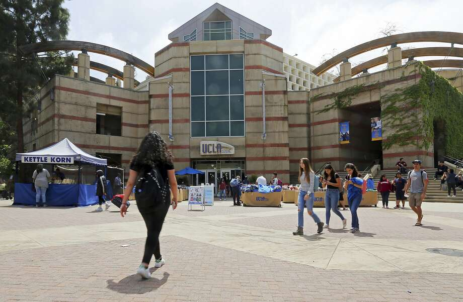 FILE - People pass Ackerman Student Union on the campus of UCLA on Friday, April 26, 2019. UCLA says Dr. James Heaps surrendered to law enforcement on Monday to face charges of sexual battery involving two patients he saw in 2017 and 2018. He worked at the clinic for nearly 30 years.  Photo: Reed Saxon, Associated Press