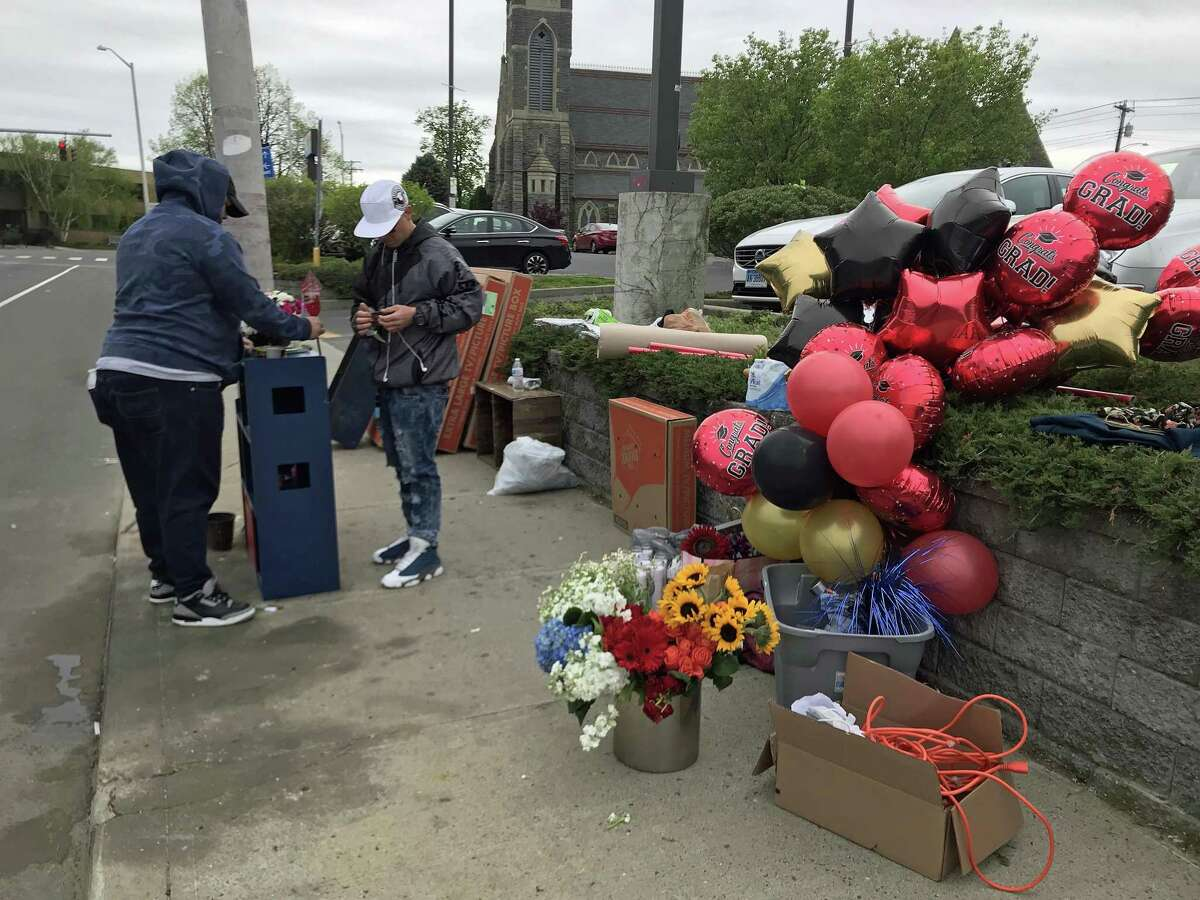 Juan Negron (right) and a relative set up balloons and a memorial on Fairfield Avenue on May 9, 2019, for 15-year-old Jayson Negron, killed two years ago on May 9, 2017.