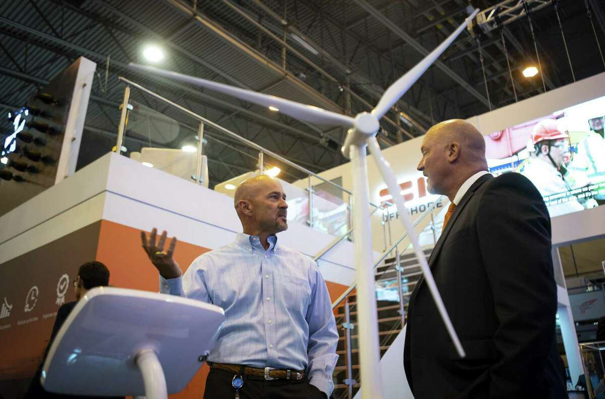 Kevin Raatz, right, with SBM Offshore, talks with Brad Reeder about the offshore wind turbine project SBM is developing, during the annual Offshore Technology Conference inside Houston's NRG Center, Tuesday, May 7, 2019. (Mark Mulligan/Houston Chronicle via AP)