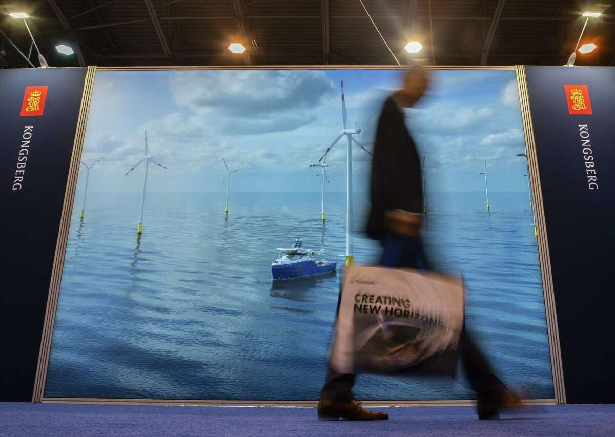 Attendees walk past the Kongsberg display that highlights offshore wind turbines during the annual Offshore Technology Conference inside Houston's NRG Center, Tuesday, May 7, 2019. (Mark Mulligan/Houston Chronicle via AP)