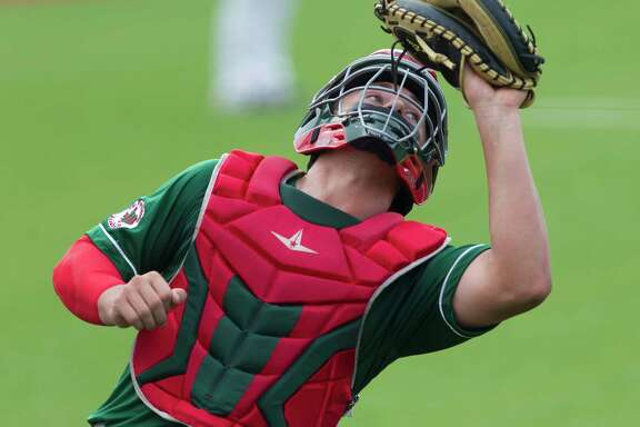 The Woodlands catcher Drew Romo (23) fields a fly ball by Dalton Bourgeois #6 of Cypress Woods in the fifth inning of Game 2 during a Region II-6A area high school baseball playoff series at Grand Oaks High School, Thursday, May 9, 2019, in Spring.