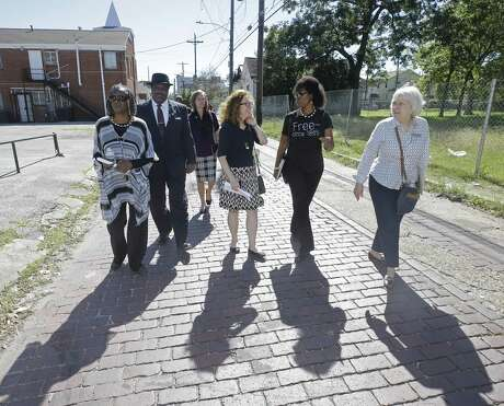 Sarah Trotty, left, Elmo Johnson, pastor of Rose of Sharon Missionary Baptist Church, Jessica Bacorn, with Houston First, Jane Landers, a UNESCO slave route project representative, Debra Blacklock-Sloan, and Catherine Roberts, with Yates Museum, right, walk on the historic bricks on Wilson St. as they toured Freedmen's Town in October of 2017, in Houston.