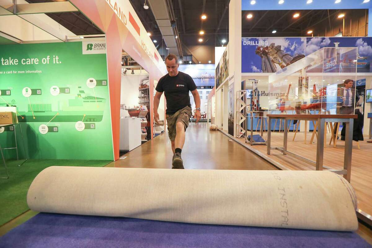 Rigo ( he only goes by one name ) from Germany rolls up carpet in front of his exhibits at the end of the Offshore Technology Conference Thursday, May 9, 2019, in Houston.