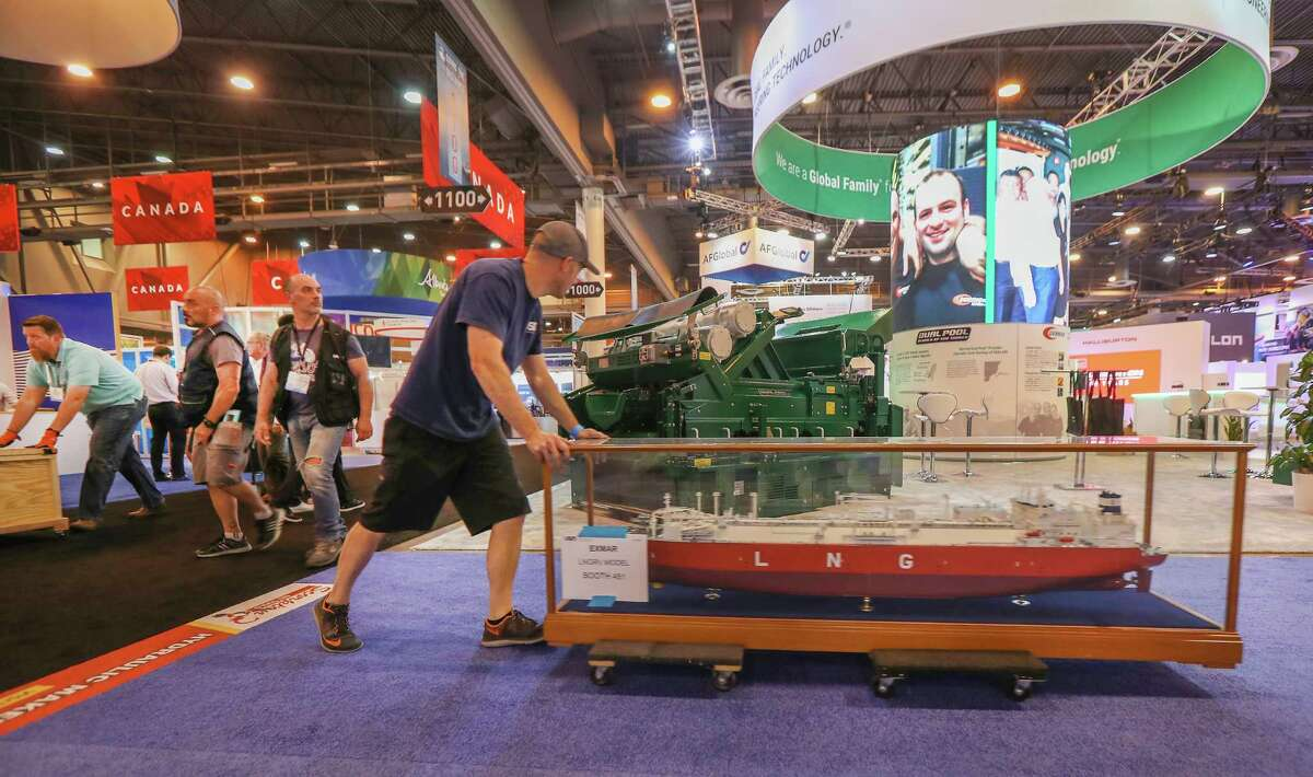 Workers move out model ships from exhibits at the end of the Offshore Technology Conference Thursday, May 9, 2019, in Houston.