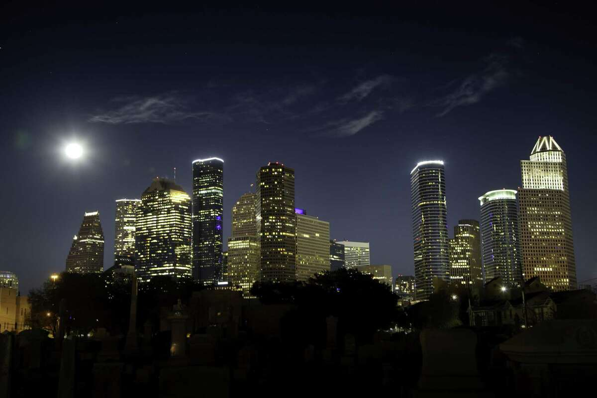 A full moon rises over the downtown Houston skyline. For the Houston economy, it's still all about oil.