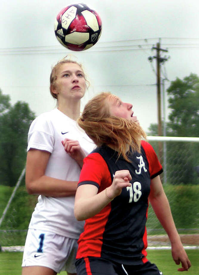 Maggie Evans of Alton (18) eyes the ball after heading it in front of Belleville East's Abigail Kuykendall Thursday night at Alton High. The Redbirds got past East 2-1 in overtime penalty kicks. Photo: Pete Hayes | The Telegraph