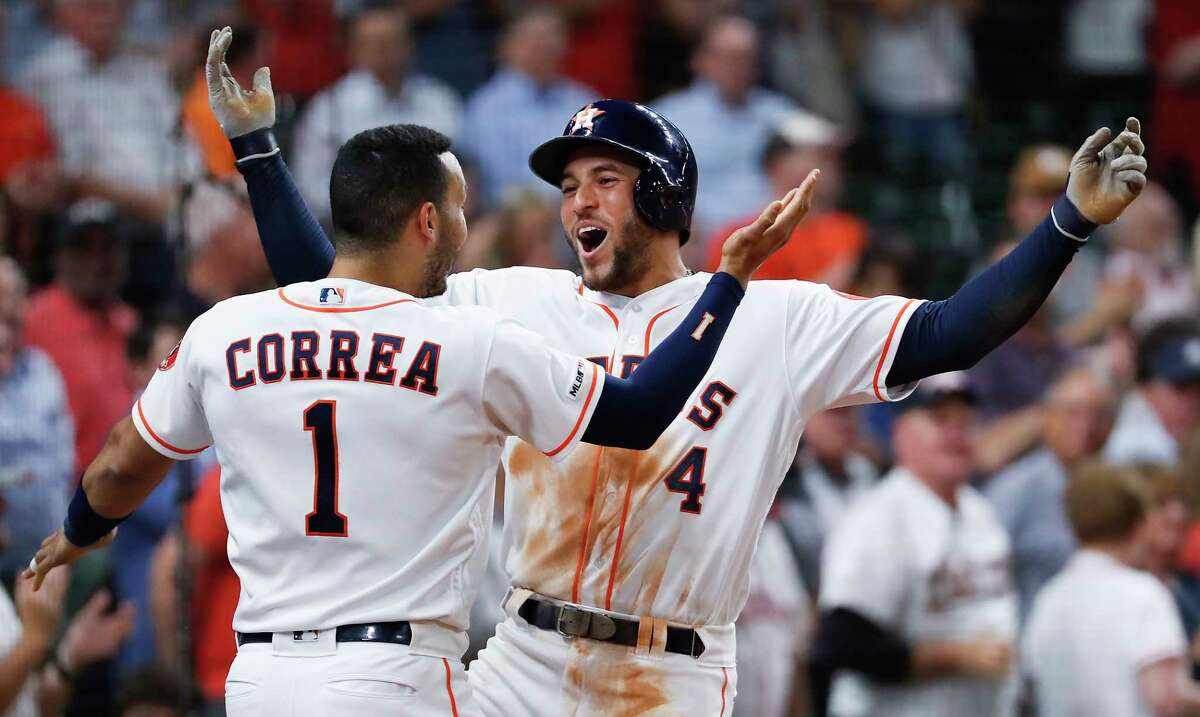 Houston Astros Carlos Correa (1) and George Springer (4) celebrate Springer's solo home run off Texas Rangers starting pitcher Mike Minor during the third inning of a major league baseball game at Minute Maid Park on Thursday, May 9, 2019, in Houston.