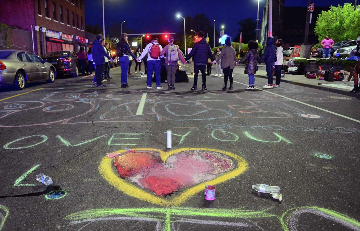 Activists and friends of Jayson Negron hold hands as they hold a vigil for him near the Walgreen's along Fairfield Ave in Bridgeport, Conn., on Thursday May 9, 2019. They were there to mark the second anniversary of Negron's death after he was shot and killed by a police officer near the pharmacy.