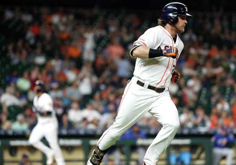 Houston Astros Josh Reddick (22) runs to first as Yuli Gurriel scores in the background after hitting an RBI single off Texas Rangers relief pitcher Ariel Jurado during the sixth inning of a major league baseball game at Minute Maid Park on Thursday, May 9, 2019, in Houston.