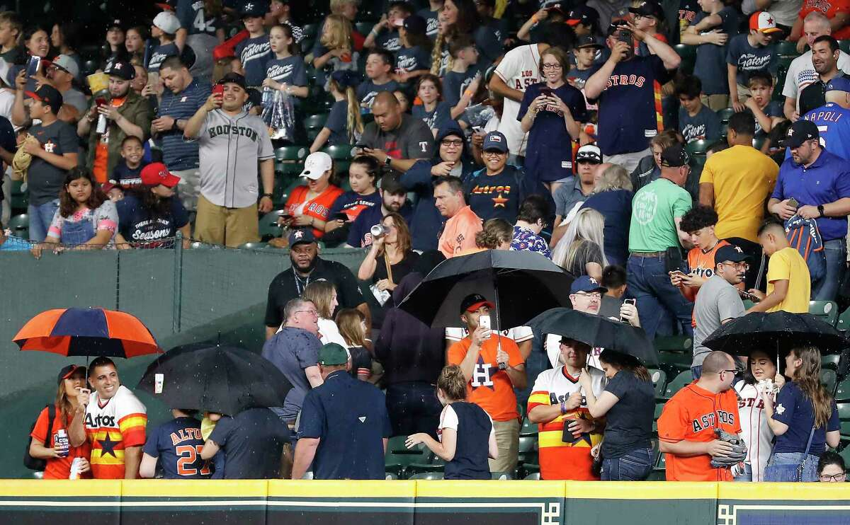 Houston Astros fans take cover under umbrellas as the heavy rain leaks into Minute Maid Park during the eighth inning in a major league baseball game between the Astros and Texas Rangers on Thursday, May 9, 2019, in Houston.