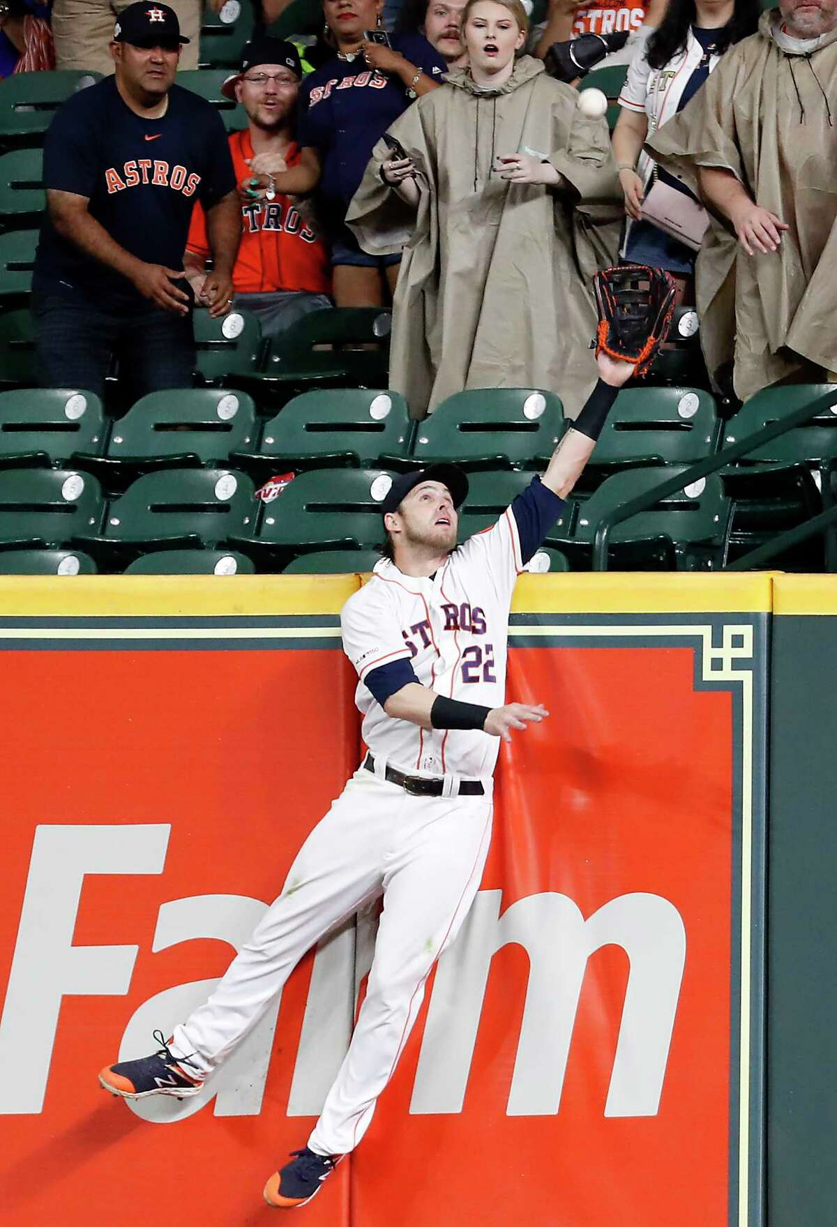 Houston Astros Josh Reddick (22) leaps to a make a catch at the wall of the bat of Texas Rangers Hunter Pence during the ninth inning of a major league baseball game at Minute Maid Park on Thursday, May 9, 2019, in Houston. Pence hit the ball to deep right with runners on first and third. Reddick's catch stopped the Rangers from scoring.