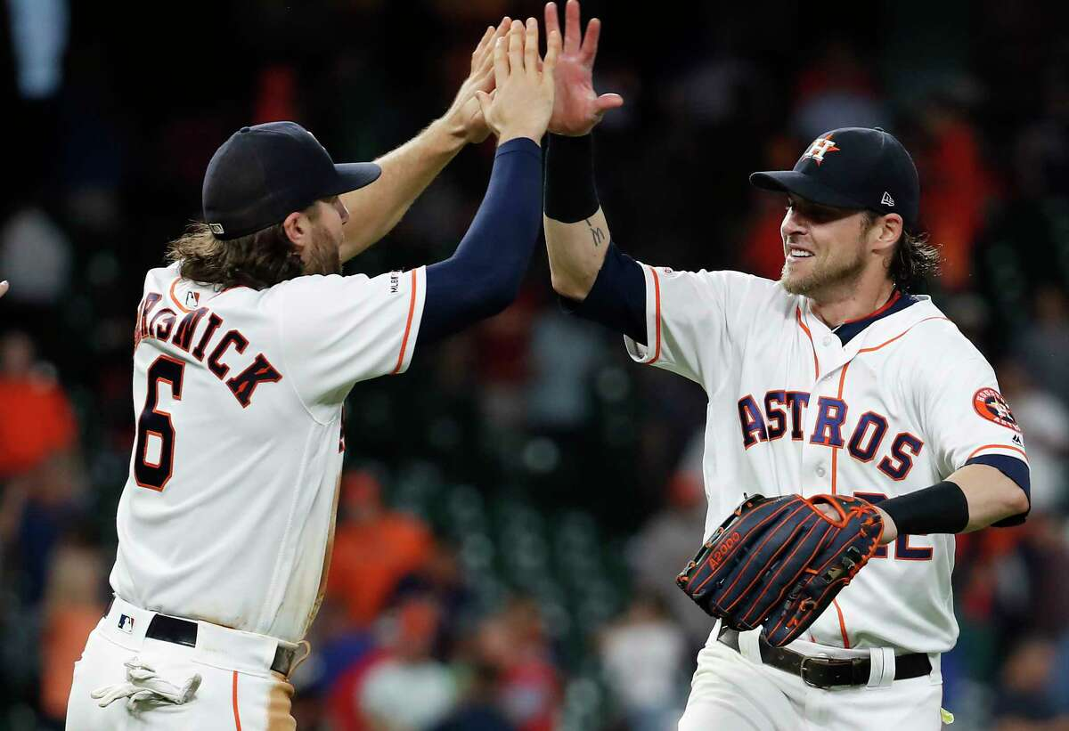 Houston Astros Jake Marisnick (6) high fives Josh Reddick (22) as they celebrate the Astros 4-2 win overt the Texas Rangers during the ninth inning of a major league baseball game at Minute Maid Park on Thursday, May 9, 2019, in Houston.