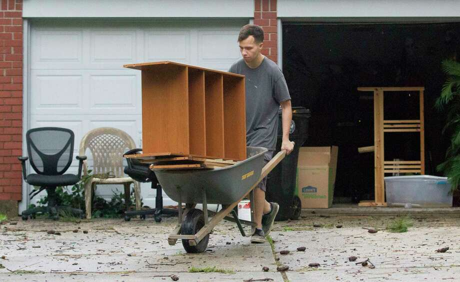Brandon Tanner helps move damaged furniture from a friend's home in the Elm Grove Village subdivision, Friday, May 10, 2019, in Kingwood. Flash flooding caused several home in the neighborhood to take in water. Photo: Jason Fochtman, Staff Photographer / © 2019 Houston Chronicle
