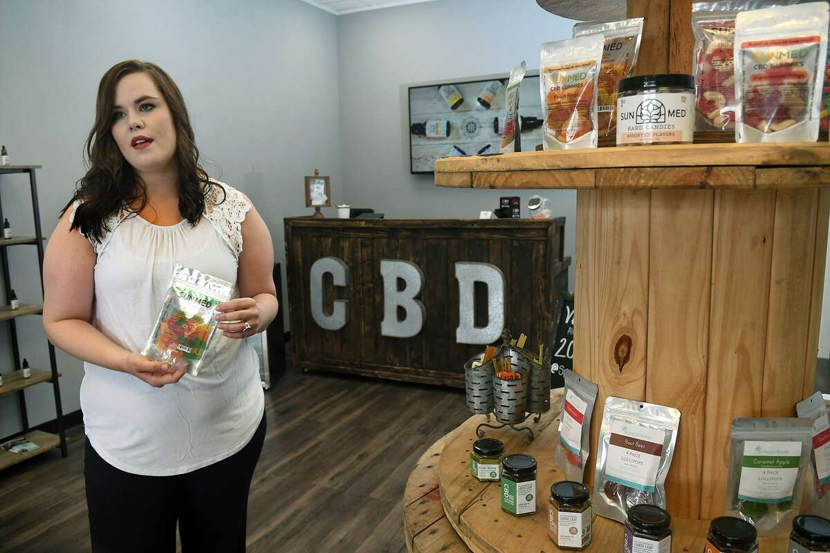 Ally Horner, Co-owner and general manager of the CBD store at 4027 FM 2920 in Spring, shows off the wide selection of SUNMED products offered at her store on May 8, 2019.