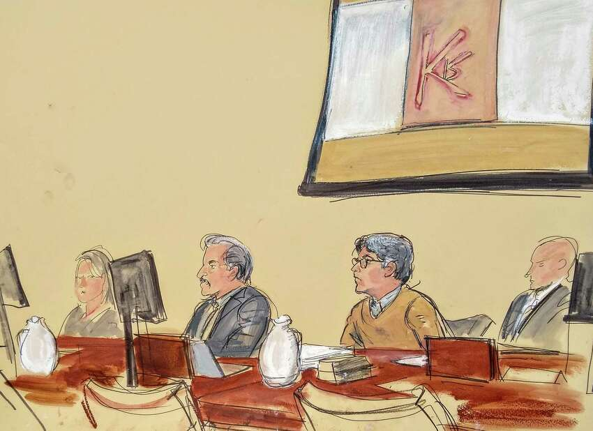 In this courtroom artist's sketch, Keith Raniere, second from right, leader of the secretive group NXIVM, attends his trial in Brooklyn federal court, Tuesday, May 7, 2019 in New York. Above him is a screen with an image of a branding, containing his initials KR. A federal prosecutor says the self-help guru used threats,