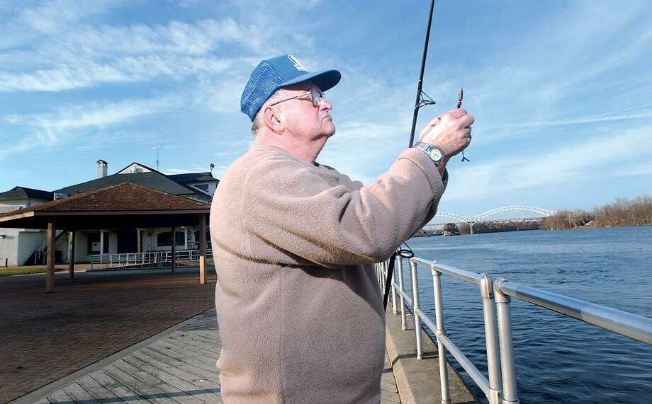 A Middletown fisherman fastens an artificial worm to his fishing line at Harbor Park, where he likes to frequent. Photo: File Photo