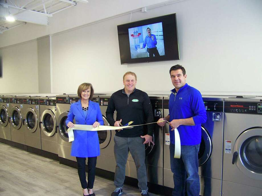 CLEANING UP: From left, Quinnipiac Chamber of Commerce Executive Director Dee Prior-Nesti, Ultra Coine 2 owner Chris Wilson and Marco Verna of Verna Properties cut the ceremonial ribbon marking the grand opening of Ultra Coin 2 laundromat at 1118 North Colony Road in Wallingford April 23. The 2,800-square-foot facility has 24 new commercial washers and 26 dryers; coins and credit/debit cards are accepted and users can receive a text message when the cycle is complete. The laundromat is open from 7 a.m. to 8 p.m. daily. Photo: Contributed Photo