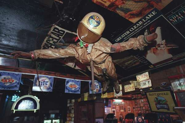 The Outpost Tavern, a legendary bar near NASA, closed in 2009 but the owners still have much of the old memorabilia and maintain hopes it could be reopened someday. Here, a flight suit and other space-related items decorate the Outpost.