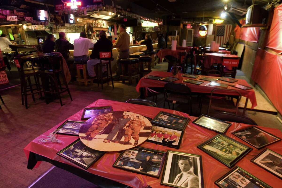 Historic photos from the space program are shown on a table at the Outpost Tavern in Webster. A NASA-area hangout for astronauts and regular folks, the bar closed in 2009 but hopes remain it could reopen someday.