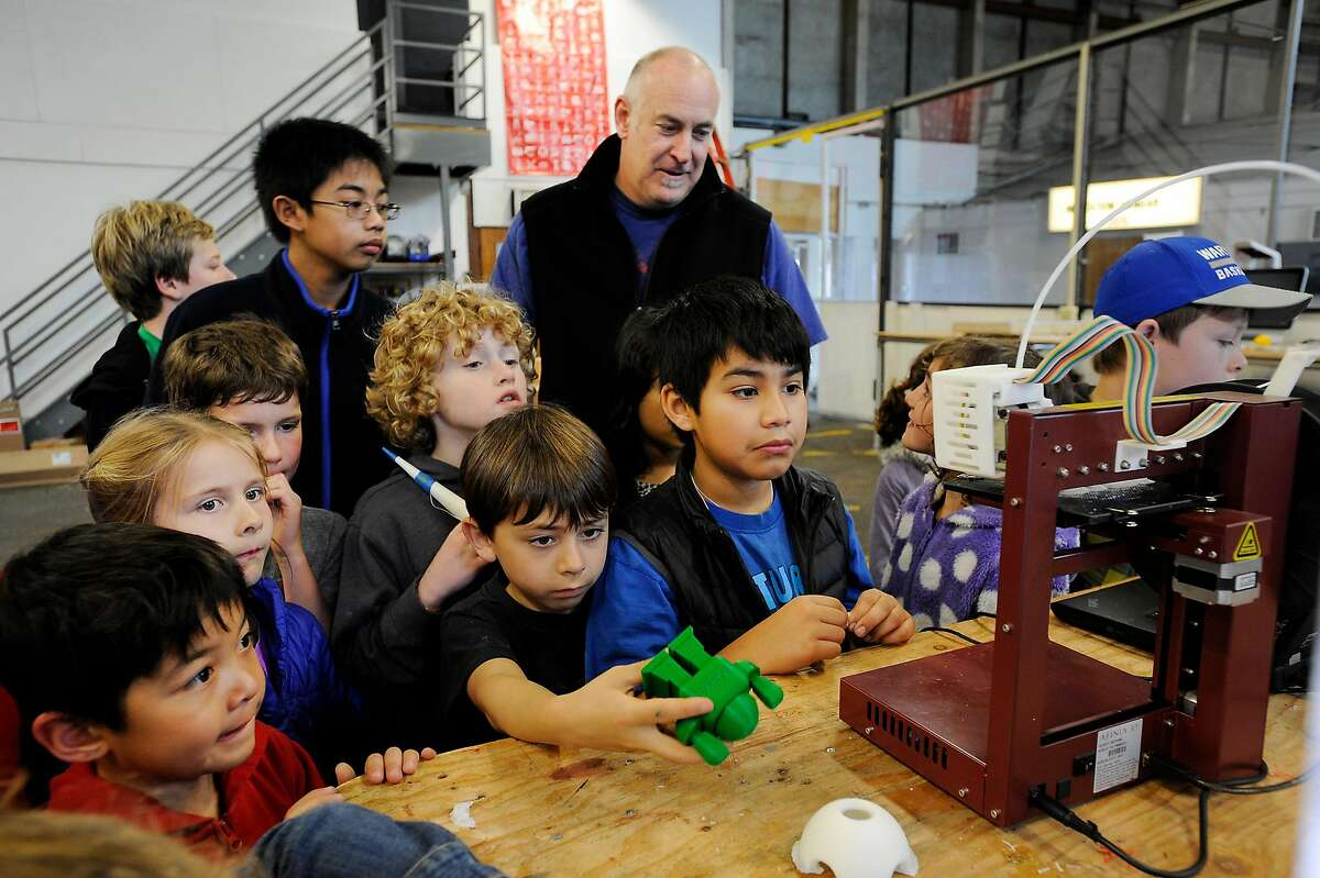 Maker Media Lab Director Marty Marfin, in back, shows students from the Presidio YMCA a 3D printer in the Maker area during a preview of the centennial celebration of the 1915 Panama Pacific Fair at the Palace of Fine Arts in San Francisco, CA, on Thursday, February 19, 2015.