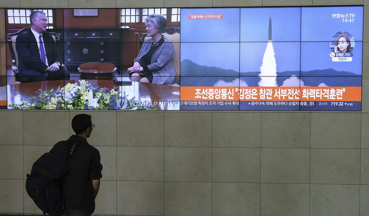 A man watches TV screens showing a photo of North Korea's weapon systems and South Korea's Foreign Minister Kang Kyung-wha meets with U.S. Special Representative for North Korea Stephen Biegun, top left, during news programs at the Yonhap News Agency building in Seoul, South Korea, Friday, May 10, 2019. The U.S. and South Korean militaries evaluated the two projectiles North Korea flew Thursday as short-range missiles, a South Korean military official said Friday, a day after the North's second launch in five days raised jitters about an unravelling detente between the Koreas and the future of nuclear negotiations between Washington and Pyongyang. The signs read: